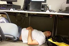 ein sehr mueder mann schlaeft im buero unter dem computer